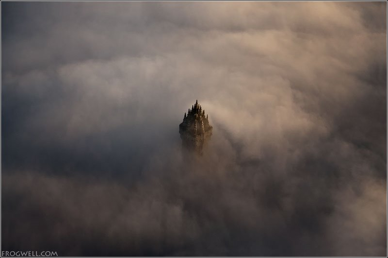 Aerial photo of the Wallace Monument peaking through low cloud.